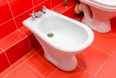 Bidé de la foto en el cuarto de baño rojo foto de archivo