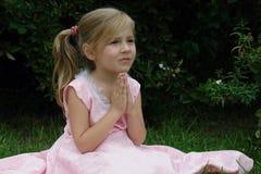 Biddend meisje op het gras Stock Afbeeldingen
