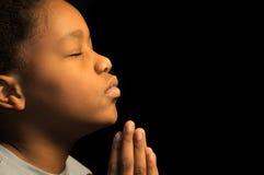 Biddende Afrikaanse jongen Americn Stock Fotografie