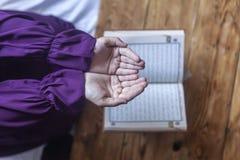 Biddende jonge moslimvrouw Meisje dat van het Middenoosten en heilige Quran bidt het leest Moslimvrouw die Quran bestuderen royalty-vrije stock foto
