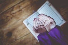 Biddende jonge moslimvrouw Meisje dat van het Middenoosten en heilige Quran bidt het leest Moslimvrouw die Quran bestuderen stock foto's