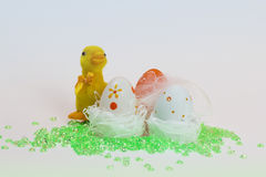 Biddy with Easter eggs. A chick guarding the colorful Easter eggs Royalty Free Stock Images