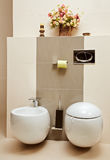 Bidet and pan in toilet room. Part of interior of toilet room with bidet and pan in beige tones Stock Photography