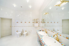 Bidet and toilet and big mirror with sinks in bathroom. Royalty Free Stock Photo