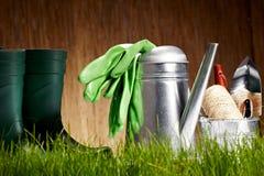 Bidon d'arrosage avec l'herbe et les outils de jardin Images stock