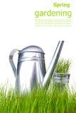Bidon d'arrosage avec l'herbe et les outils de jardin Photos libres de droits