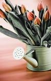 Bidon d'arrosage complètement de fleurs Photos stock