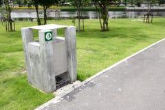 Bidon d'ordures vert sur une herbe de jardin photos stock