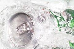 Bidon de bière éclaboussant l'eau Photographie stock libre de droits