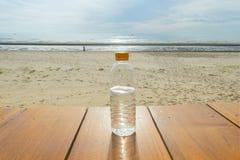 Bidon na drewnianej podłoga na morza niebieskiego nieba i plaży tle Obraz Stock