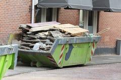 Bidone della spazzatura caricato vicino al cantiere Fotografia Stock