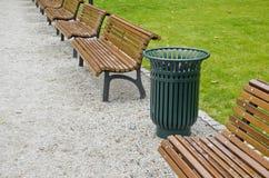 Bidone della spazzatura e banco di legno nel parco della città Immagine Stock