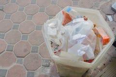 Bidone della spazzatura fuori di un deposito in cui il passo della gente ha ordinato i rifiuti, Fotografia Stock