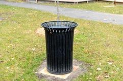 Bidone della spazzatura nero nel parco pubblico Fotografia Stock Libera da Diritti