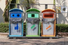 Bidone della spazzatura in tricromia situato nei luoghi pubblici fotografia stock libera da diritti