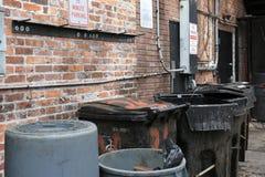 Bidoni della spazzatura in vicolo posteriore della città fotografia stock libera da diritti