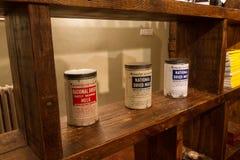 Bidons de lait en poudre sur une étagère Images stock