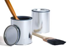 Bidons neufs de peinture avec des balais Photo stock