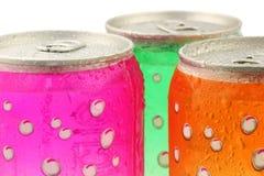 Bidons pétillants colorés de boissons avec des gouttelettes d'eau Photos stock
