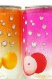 Bidons pétillants colorés de boissons avec des gouttelettes d'eau Images stock