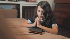 Bidt de meisje heilige bijbel levensstijl met bijbel in haar handen de katholicisme heilige heilige bijbel Kinderen en stock videobeelden