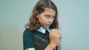 bidt de meisje heilige bijbel met bijbel in haar handen de katholicisme heilige heilige bijbel Kinderen en godsdienst stock videobeelden