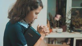 bidt de meisje heilige bijbel met bijbel in haar handen de bijbel van de katholicisme heilige heilige levensstijl Kinderen en stock video