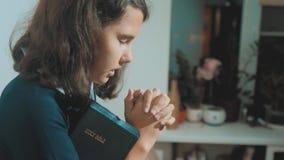 Bidt de meisje heilige bijbel met bijbel in haar handenlevensstijl de katholicisme heilige heilige bijbel Kinderen en stock video