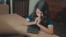 Bidt de meisje heilige bijbel met bijbel in haar levensstijlhanden de katholicisme heilige heilige bijbel Kinderen en stock footage