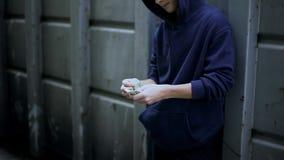 Biedna chłopiec skrycie liczy gotówkę od kieszeni, ubóstwo w żebraka terenie, depresja obrazy royalty free