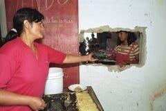 Biedna głodna Argentyńska młodość je w zupnej kuchni zdjęcie stock
