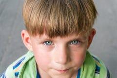 Biedna i nieszczęśliwa chłopiec płacze z łzami w jego oczach i pyta dla pomocy podczas gdy patrzejący w kamerę zdjęcia stock