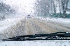 Biedna widoczność na drodze samochód przejażdżki na śliskiej drodze śnieg i deszcz na przedniej szybie zamazujący tło Zła pogoda obrazy stock