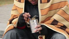 Biednego głodnego faceta łasowania konserwować jedzenie, myśleć o życiu, ubóstwo, bezdomność zdjęcie wideo