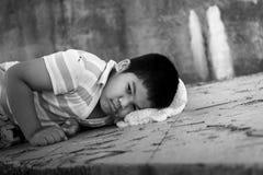 Biednej chłopiec smutny lying on the beach na brudnej podłoga zdjęcia stock