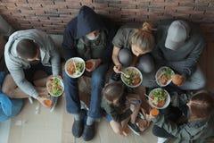 Biedni ludzie z talerzami karmowy obsiadanie przy ?cian? indoors fotografia stock