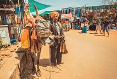Biedny azjatykci muzyk z fletem bawić się piosenki dla pieniądze i krowy jedzenia na tradycyjnej targowej ulicie Obrazy Stock