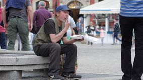 Biedny bezdomny mężczyzna je od klingerytu talerza obsiadania na ulicie zbiory wideo