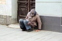 Biedny bezdomny mężczyzna obsiadanie blisko ściany budynek zdjęcia royalty free