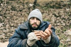 Biedny bezdomny mężczyzna z filiżanką w parku zdjęcia stock