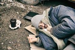 Biedny bezdomny mężczyzny lying on the beach na ziemi obraz stock
