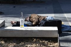 Biedny bezdomny pijący obsługuje dosypianie na podłodze ulica na tle pusta butelka wino Barcelona obrazy stock