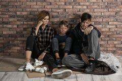 Biedny bezdomny rodzinny obsiadanie na podłodze zdjęcia stock