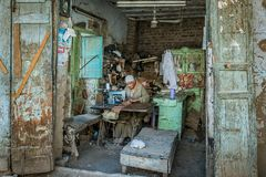 Biedny egipcjanina krawczyna używa jego starą szwalną maszynę w prostym hovel zdjęcie stock