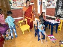 Biedny rz?dowy preschool nauczyciel i jej grupa dzieciaki podnosi ich r?ki i ma niekt?re zabaw? przy szko?? zdjęcia royalty free