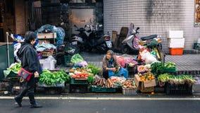 Biedny stara kobieta sprzedawca sprzedaje warzywa na Tajwańskiej ulicie obrazy stock