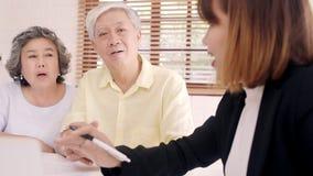 Biedt de slimme vrouwelijke agent van Azië ziektekostenverzekering voor bejaarde paren door document, tablet en laptop aan Het ou stock video
