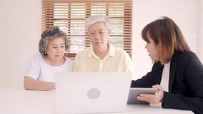 Biedt de slimme vrouwelijke agent van Azië ziektekostenverzekering voor bejaarde paren door document, tablet en laptop aan Het ou stock footage
