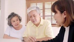 Biedt de slimme vrouwelijke agent van Azië ziektekostenverzekering voor bejaarde paren door document, tablet en laptop aan Het ou stock videobeelden