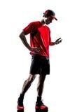 Biegaczów joggers smartphones hełmofonów sylwetki obrazy stock